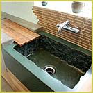 Concrete sink with rough edges and wooden drainboard